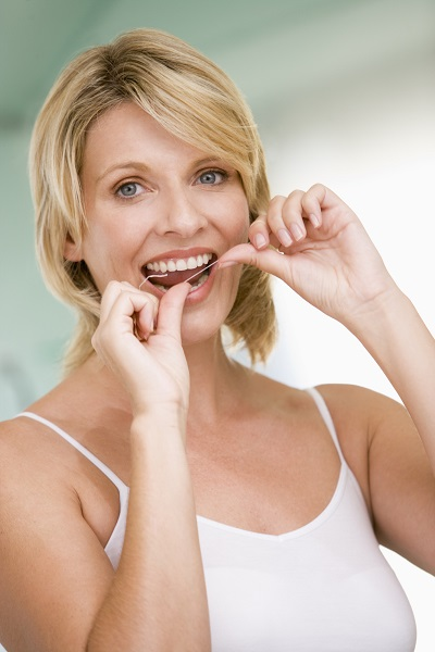 A woman flossing to remove food from between her teeth.